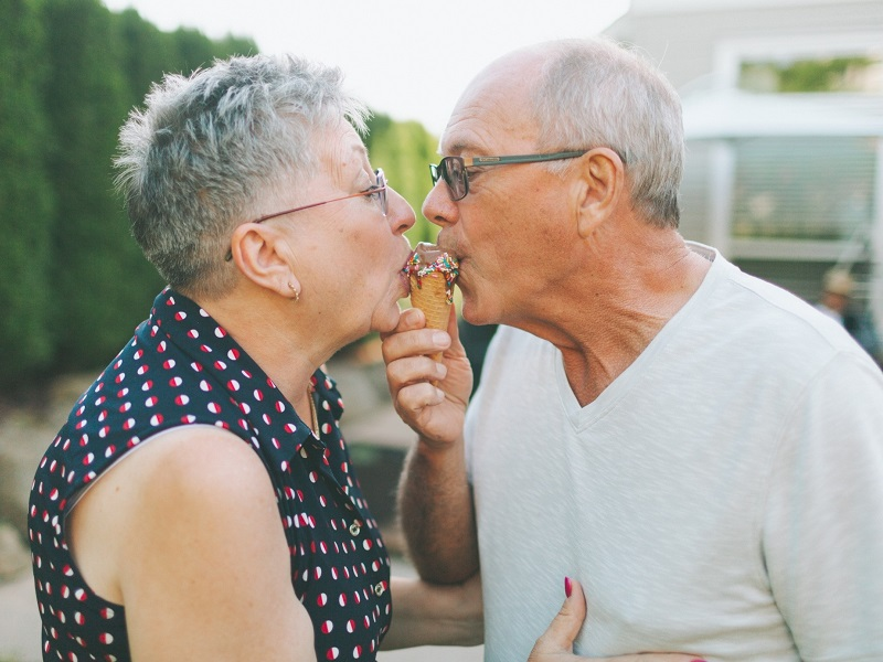 mature couple who met on one of the dating sites for seniors over 50 kissing and eating an ice-cream