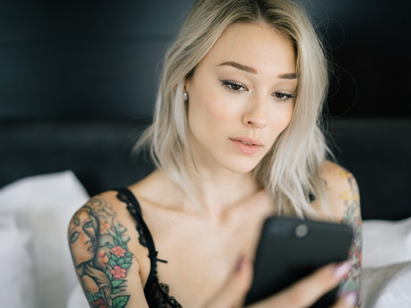 Attractive woman sitting on bed sending a sexting text