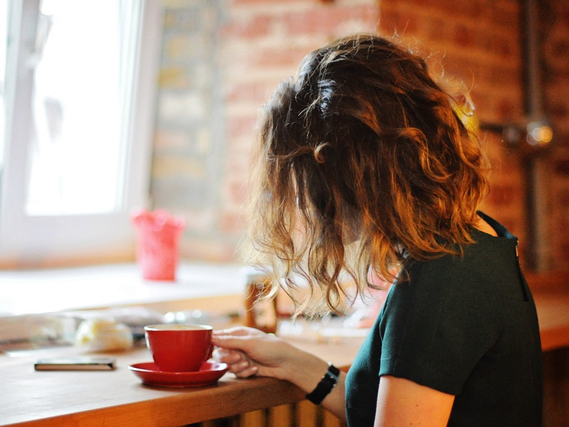 woman sitting in cafe drinking coffee wondering why am I single?