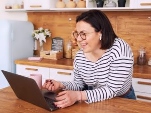 lady standing in kitchen with laptop trying out virtual date ideas