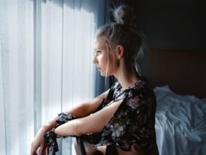 a woman in a bedroom lost in thought about how to break up with someone nicely
