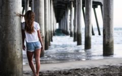 woman standing under a pier thinking about toxic relationship definitions