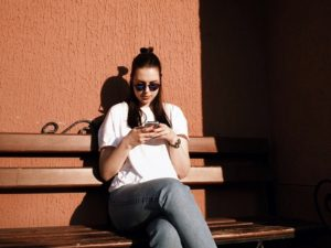 woman sitting on a bench typing her best hinge answers on her mobile phone