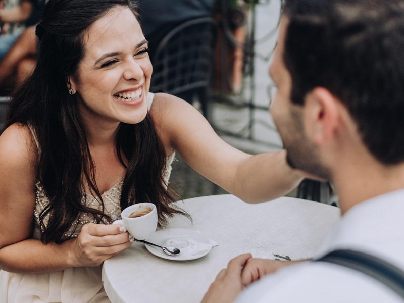 couple drinking coffee and laughing showing the signs she wants a serious relationship with you