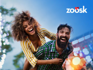 attractive couple who met on Zoosk dating laughing outside with her on his back