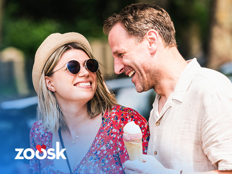 Man and woman laughing while they have ice cream and are Zoosk singles on a date