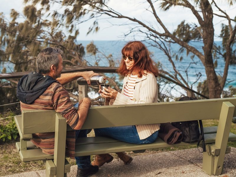 man and woman drinking coffee on bench enjoying +40 dating