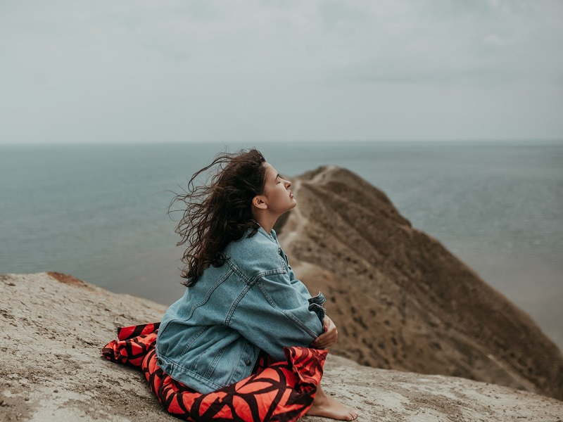 woman sitting on mountain exploring how to get over someone fast