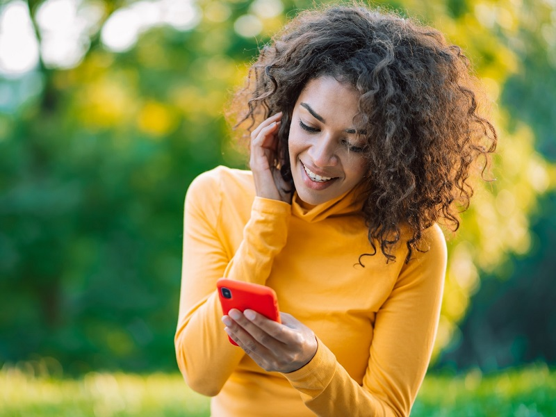attractive woman using mobile phone to send love texts for him