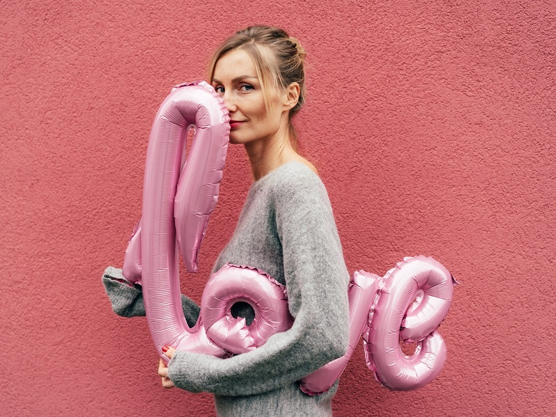 Woman smiling with love balloon on Valentine's Day 2021