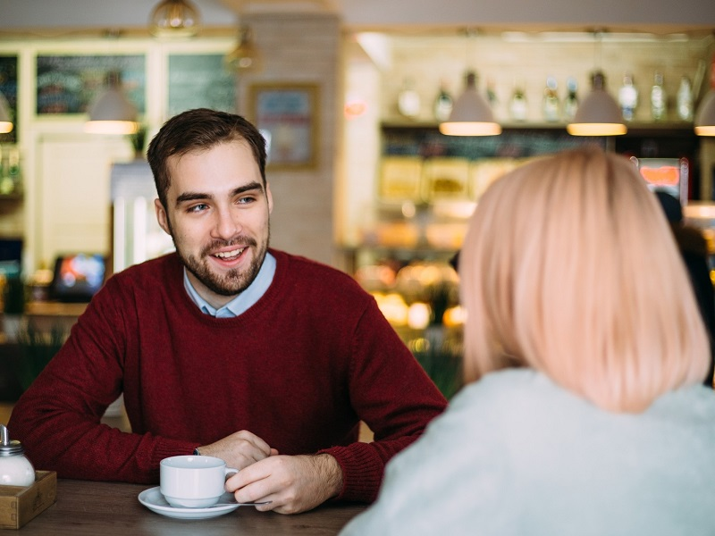 attractive man looking at a woman and flirting in conversation at a coffee shop
