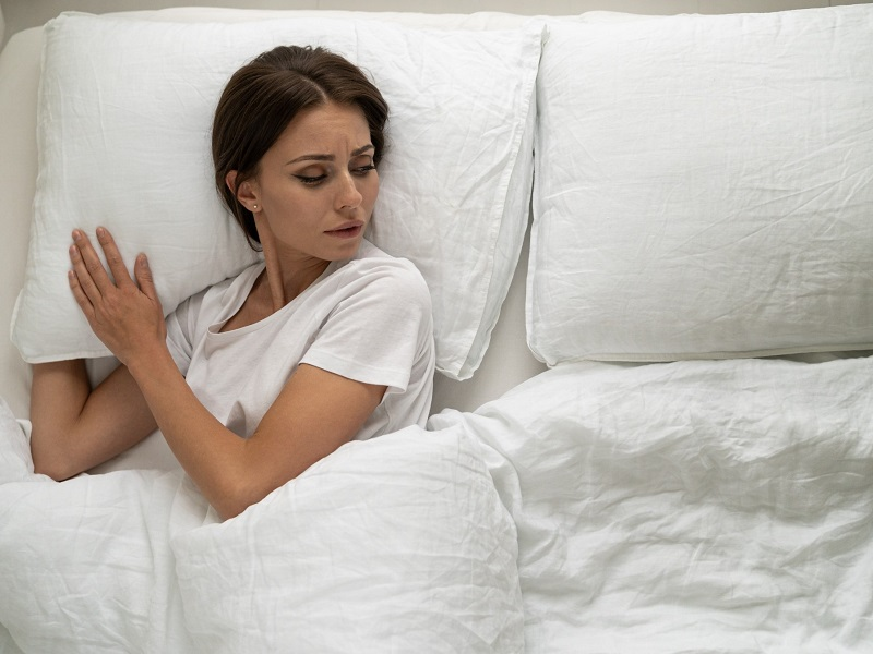 woman lying alone in bed looking sad after facing common relationship problems